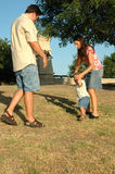 Let's Walk. Mom holds up her babies arms as he learns how to walk at a park stock image