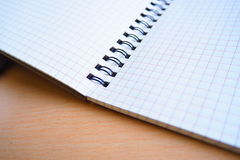 Let`s write on a note book. An opening grid-page note book on a desk Royalty Free Stock Photos