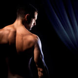 Let the show begin. A muscular man showing his back under dramatic lights Stock Photo