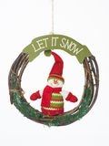 Let it snow christmas wreath. Closeup of hanging christmas wreath with funny dressed snowman with the message let it snow, isolated on white stock image