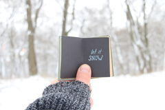 Let it snow concept, book with text. Let it snow. Hand holding a book with the inscription royalty free stock photos