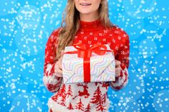 Let it snow! Cropped photo of happy charming joyful girl giving. A giftbox. She is on blue background with snowflakes stock photos