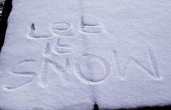 Let It Snow. Drawn with fingers into snow royalty free stock photos