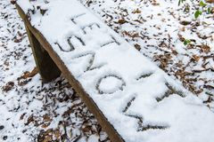 Let it Snow lyric writtten on snow covered bench. `Let it Snow` lyric/Christmas message written in snow on a bench stock photo