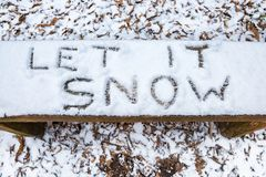 Let it Snow lyric writtten on snow covered bench. `Let it Snow` lyric / Christmas message written in snow on a bench stock photo