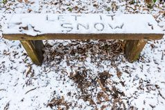 Let it Snow lyric writtten on snow covered bench. `Let it Snow` lyric/Christmas message written in snow on a bench stock photography