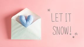 Let It Snow message with a blue heart cushion. In an envelope royalty free stock photo