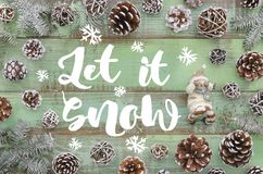 Let it snow and snowman on green wooden plank background with pine cones and fit tree, winter new year greeting card. Banner, top view flat lay royalty free stock image