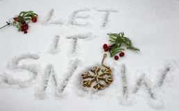 Let it snow. Words let it snow written in snow with holiday season berries ornaments and snowflake for snowstorm or snow weather social shareimage royalty free stock photos