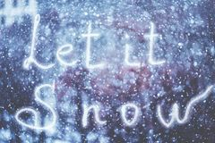 Let it Snow, written by hand on the snowstorm winter background, toned.  stock photo
