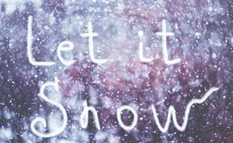 Let it Snow, written by hand on the snowstorm winter background, toned.  royalty free stock photography