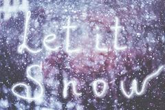 Let it Snow, written by hand on the snowstorm winter background, toned.  stock image