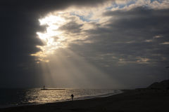 Let the sunrise. Coastal landscape during a sunset, some sunshine through the clouds escape Royalty Free Stock Image