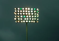 Let There Be Light. A photograph of a bank of stadium lights against a dark cloudy sky Royalty Free Stock Images