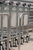 Let us carry your luggage!. Row of luggage carts at the airport Royalty Free Stock Images