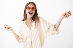 Let us enjoy life. Portrait of joyful happy and amused carefree stylish woman in trendy red sunglasses and yellow. Striped blouse dancing singing song out loud stock photo