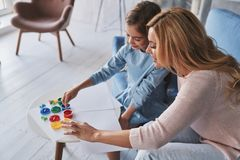 Let us learn something new! Top view of mother and daughter touching paints and smiling while spending time at home royalty free stock photo
