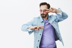 Let us lit this dancefloor. Charming flirty and emotional good-looking male in denim jacket and stylish sunglasses. Dancing and making disco gesture or peace Stock Images
