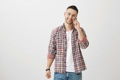 Let us meet together at seven. Portrait of handsome young successful man in trendy clothes talking on smartphone while. Being in good mood standing against gray Royalty Free Stock Photo