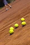 Let us play. Tenis balls on court with young player in the back Royalty Free Stock Photos