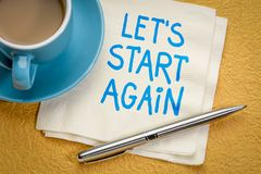 Let us start again note. Let`s start again note - motivational handwriting on a napkin with a cup of coffee royalty free stock images