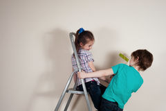 Let us start painting. Boy and girl  with paddle rollers making renovation in the house Royalty Free Stock Photos