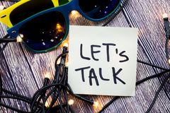 Let us talk handwritten on a paper with black color. 2 glasees in colors with lights in the random order with wooden background. C. Let us talk handwritten on stock images
