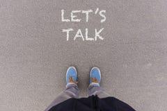 Let us talk text on asphalt ground, feet and shoes on floor Royalty Free Stock Photos