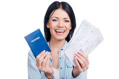 Let us travel!. Beautiful young smiling woman holding tickets and passport while standing against white background Stock Photo