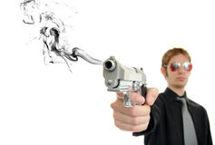 Lethal Weapon. Young man holds his pistol out and shoots out smoke Royalty Free Stock Photo