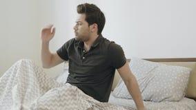 Lethargischer Mann, der langsam am Morgen aufwacht Hübscher Kerl, der auf Bett sitzt stock footage