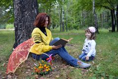 Letnic vacatireading的秋天画象微笑室外两个儿子婴孩爱自然乐趣父亲微笑的女儿户外妇女孩子h 图库摄影