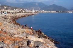 Letnicy zaludniają i rybacy na kamiennym jetty Obraz Stock