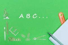 Letra ABC, miniaturas de madera de las fuentes de escuela, cuaderno con la regla, pluma en tablero trasero verde Imagenes de archivo