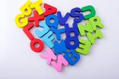 A letra colorida obstrui o coração da forma Imagens de Stock Royalty Free