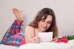 Letra da leitura na cama com pyjamas e as rosas cor-de-rosa Fotografia de Stock Royalty Free