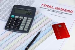 Letra da procura final em uma mesa com um cartão de crédito e uma calculadora Fotografia de Stock Royalty Free