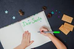 Letra de la escritura del pequeño niño a Santa Claus en una hoja de papel en blanco Foto de archivo