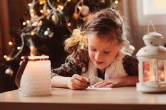 Letra de la escritura de la muchacha del niño a Papá Noel en casa 8 años de la muchacha que hace la lista de regalo por la Navida Foto de archivo libre de regalías
