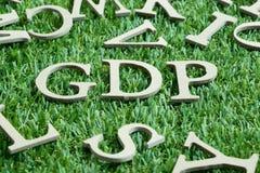 Letra de madeira na abreviatura da palavra GDP da boa prática da distribuição ou produtos internos brutos na grama verde artifici fotografia de stock royalty free
