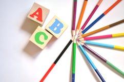 A letra de madeira obstrui o alfabeto ABC com lápis coloridos imagens de stock