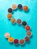 Letra de S de superfoods en cuenco en fondo azul Fotografía de archivo libre de regalías