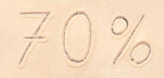letra del 70% escrita en la arena de la playa Imagen de archivo