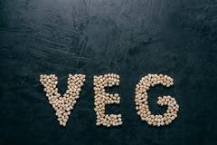 A letra deu forma ao grão-de-bico seco para vegetarianos no fundo escuro com espaço da cópia Conceito saud?vel natural do aliment fotografia de stock