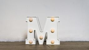Letra do alfabeto Luz da noite no berçário A letra branca M com luminoso está no assoalho imagens de stock