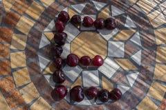 Letra E hecha con los cherrys para formar una letra del alfabeto con las frutas Fotografía de archivo libre de regalías