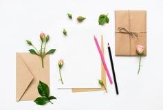Letra, envelope e presente no fundo branco Cartões do convite, ou carta de amor com rosas cor-de-rosa Conceito do feriado, vista  Fotografia de Stock