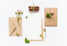 Letra, envelope e presente no fundo branco Cartões do convite, ou carta de amor com rosas cor-de-rosa Conceito do feriado, vista  Fotos de Stock Royalty Free