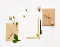Letra, envelope e presente no fundo branco Cartões do convite, ou carta de amor com rosas cor-de-rosa Conceito do feriado, vista  Imagem de Stock