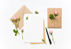 Letra, envelope e presente no fundo branco Cartões do convite, ou carta de amor com rosas cor-de-rosa Conceito do feriado, vista  Imagem de Stock Royalty Free